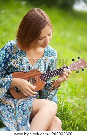 Young Woman In Bohemian Dress Play On Ukulele