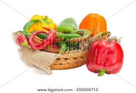 Red and green chili and several multi-colored bell peppers on a sackcloth in small wicker basket and beside on a white background