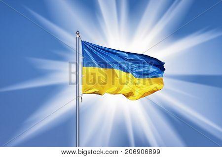 Ukrainian flag on blue sky backgroud snd big sun