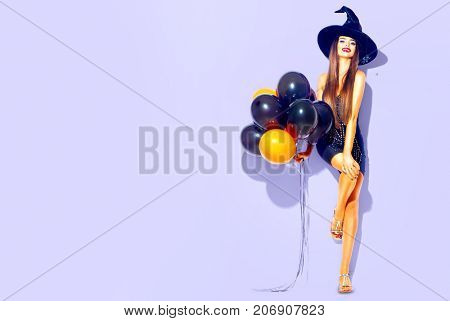 Halloween Party girl. Happy Halloween Sexy Witch with Air balloons. Beautiful young surprised woman in witches hat and costume holding black and orange air balloons. Over violet background