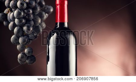 Wine. Bottle of Red wine with ripe grapes still life. Red wine Over black background. Border art design