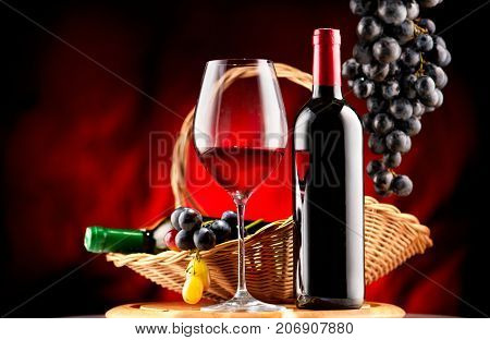 Wine. Bottle and glass of Red wine with ripe grapes still life. Red wine Over black background. Border art design