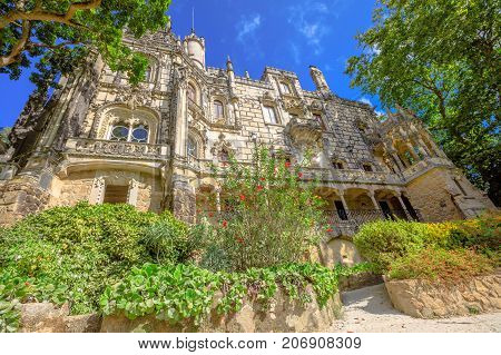 Regaleira Palace, gothic facade of grand house and gardens of famous landmark and Unesco Heritage in historic center of Sintra, Portugal. Sunny day, blue sky. Bottom view of Quinta da Regaleira.