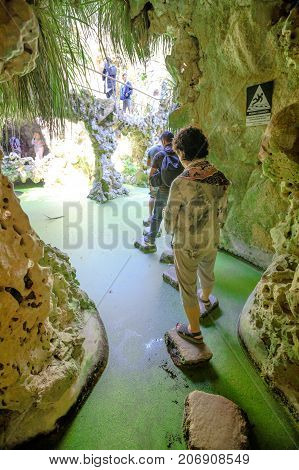 Sintra, Portugal - August 9, 2017: tourists crossing the Waterfall Lake within the park of Quinta da Regaleira or Regaleira Palace, famous landmark and Unesco Heritage in the center of the city.