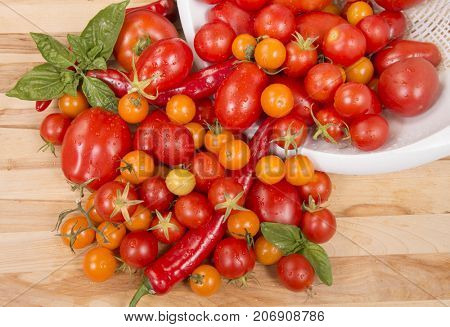 Fresh tomatoes, peppers, with basil spilling out onto a cutting board