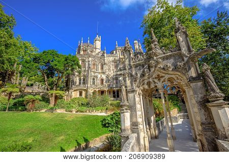 Gothic facade of grand house of Regaleira Palace, in Portuguese Quinta da Regaleira, and its gardens, famous landmark and Unesco Heritage in historic center of Sintra, Portugal. Sunny day, blue sky.