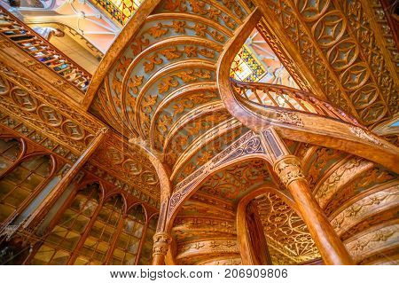 Oporto, Portugal - August 13, 2017: large wooden staircase built in 1869 by architect Xavier Esteves inside Library Lello and Irmao, historic center of Porto, famous for Harry Potter. Horizontal shot.