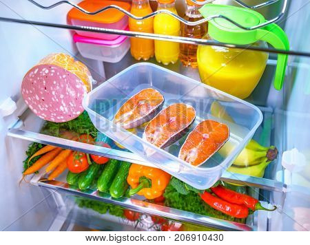 Raw Salmon steak in the open refrigerator