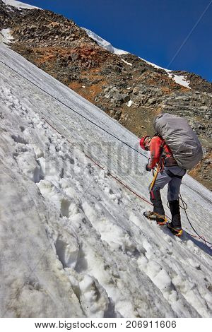 Alpinist climbing a mountain with snow field