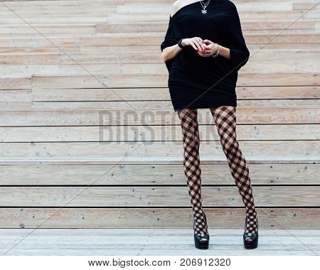 A long-legged girl in fashionable pantyhose, a black dress and black high-heeled shoes posing in the summer on wooden steps. Fashion. On the street. Part of body.