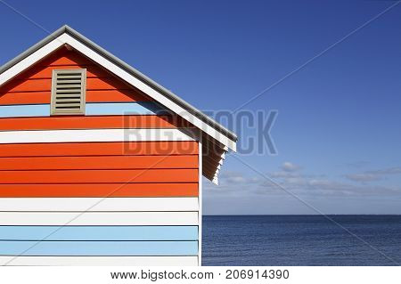 One colorful beach hut on Melbourne's iconic Brighton Beach with blue skies and ocean background