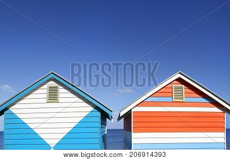 Two beach huts on Melbourne's Brighton Beach with a blue sky and ocean background