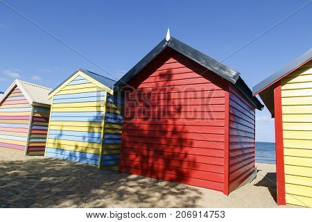 Colorful beach huts on Brighton Beach in Melbourne, Australia. Vibrant summer blue skies in the background