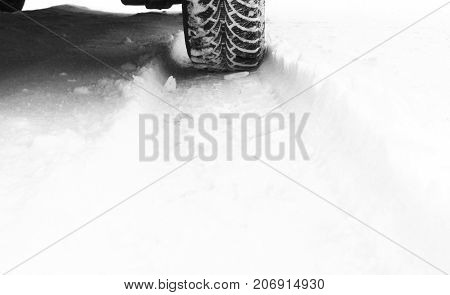 Winter tire on snow background close up