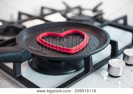 A man cooks an omelette in a beautiful kitchen on a gas cooktop in a heart shaped form. Conceptual photo