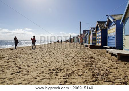 Brighton Beach, Australia: March 31, 2017: A tourist takes a photo of her friend by the colorful beach huts on Brighton Beach in Melbourne. Unidentified people walk down the beach.