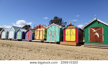 Brighton Beach, Australia: March 31, 2017: Blue skies and the colorful beach huts on Brighton Beach in Melbourne. Famous for its iconic and expensive beach huts.