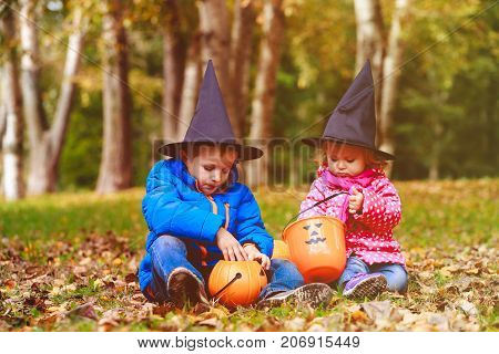 little boy and girl in halloween costume play in nature, trick or treating