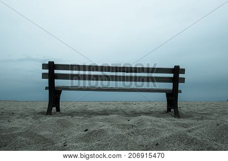Old empty bench stands on sandy beach at a dull evening, Malia, Crete, Greece