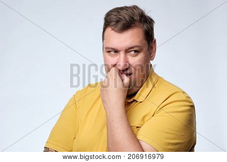 Worried fat caucasian man tries to remember something. He is worried and looks with doubt