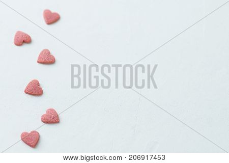 Pink Red Sugar Sprinkles Candies in Heart Shape Scattered on White Background Border Frame. Valentine Romance Birthday Charity Symbol. Greeting Card Poster Template