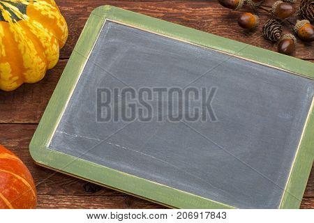 blank slate blackboard against rustic barn wood with winter squash - fall holidays theme
