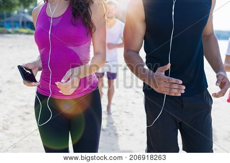 Closeup Shot Of People Running On Beach, Young Sport Runners Jogging Group Together Working Out At Seaside, Fit Male And Female Joggers Multiracial