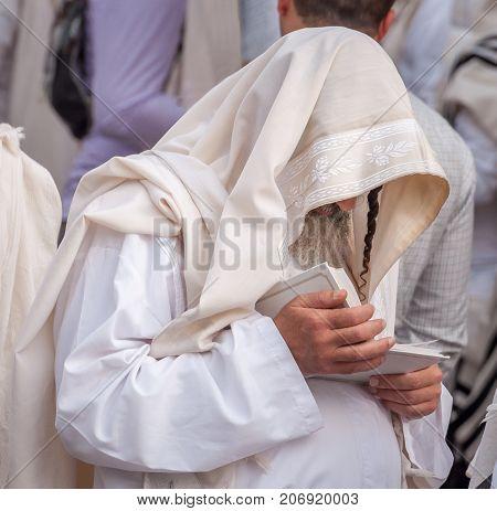 Orthodox hassidic Jew pray in a holiday robe and tallith. Uman, Ukraine - 21 September 2017: Rosh Hashanah, Jewish New Year.