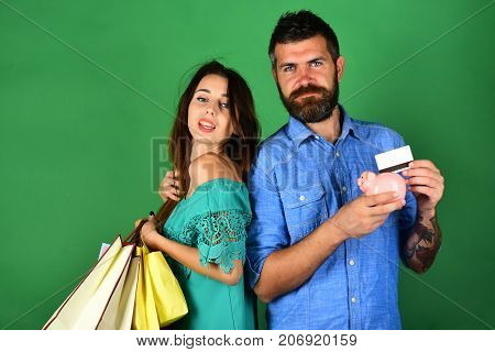 Couple In Love Holds Shopping Bags On Green Background.