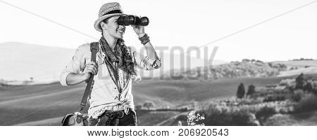 Woman Hiker In Tuscany Looking Into Distance Through Binoculars
