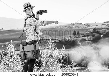 Woman Hiker With Binoculars In Tuscany Pointing At Something