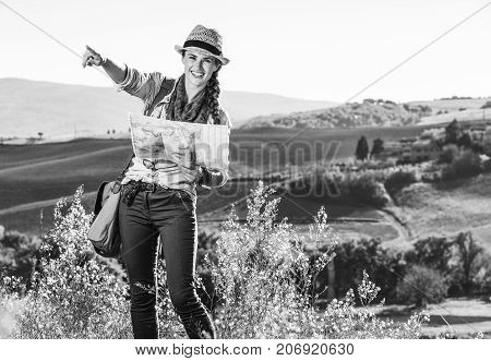Discovering magical views of Tuscany. happy young woman hiker with bag on Tuscany hike holding map and pointing