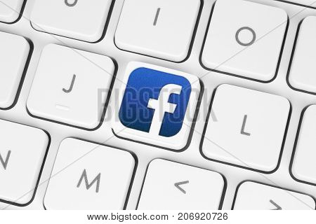 Kiev Ukraine - May 06 2016: Facebook logo printed on paper and placed on white computer keyboard. Facebook is a well-known social networking service