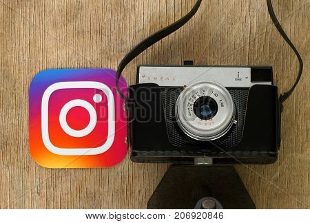 Kiev Ukraine - September 4 2017: Instagram logo printed on paper and put near retro photo camera on wooden background. Instagram is a mobile photo-sharing application and service