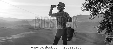 Woman Hiker Looking Into The Distance Through Binoculars