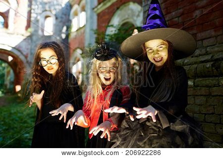Excited halloween witches with frightening gesture