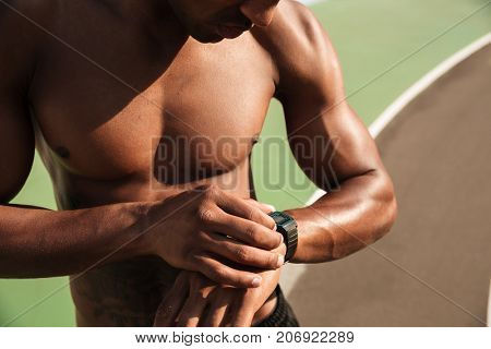 Cropped photo of half naked afro american musculary sports man checking time on wristwatch after workout