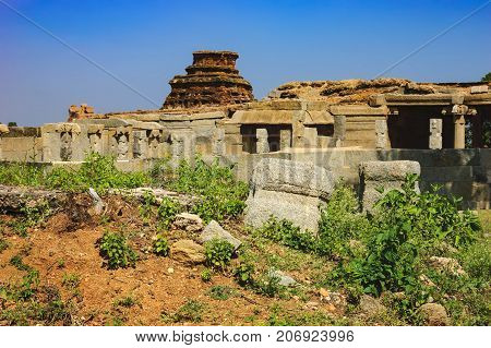 Tourist Indian landmark Ancient ruins in Hampi. Beautiful nature scenery with bright blue sky and strange landscape with large rocks, Hampi, India