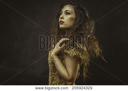 Glance, beautiful brunette woman with long brown hair dressed in gold suit, sensual and elegant poses
