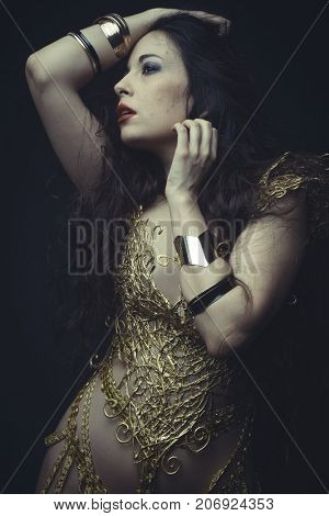Girl in dress made of golden threads with golden mask, beautiful young brunette