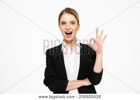 Happy blonde business woman showing ok sign and looking at the camera with open mouth over white background