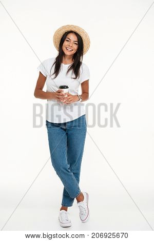 Full length portrait of a smiling casual woman in hat holding take away coffee cup while standing isolated over white background