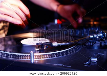 turntable, hand of dj on the vinyl record in the nightclub