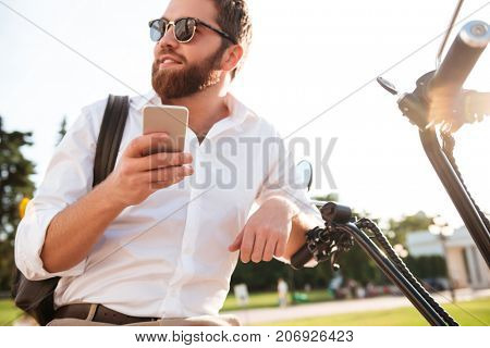 View from below of smiling bearded man in sunglasses sitting on modern motorbike outdoors and holding smartphone while looking away