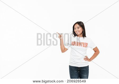 Portrait of a smiling joyful asian woman in volunteer t-shirt standing and pointing finger away at big copy space isolated over white background