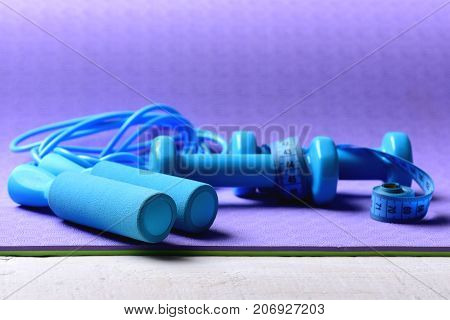 Barbells And Skipping Rope Tied With Measure Tape Roll.