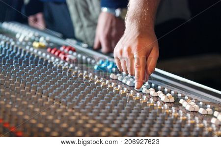 hand of sound engineer on the sound mixer in the nightclub