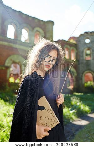 Asian girl with book and magic stick wearing black warlock