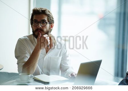 Pensive man with notepad and laptop planning work in office