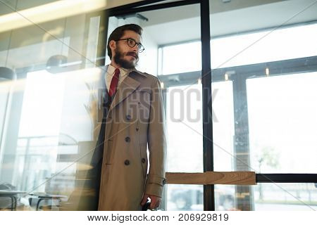 Stylish businessman in beige trench-coat, suit and red tie just entered cafe to for drink or lunch